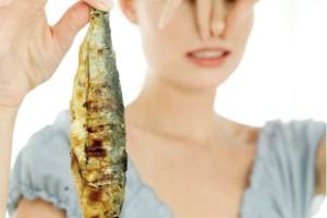 женщина держит испорченную рыбу