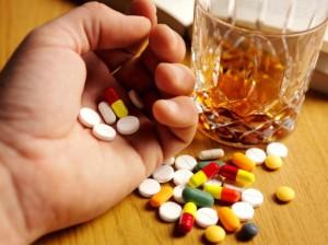 стакан возле руки с таблетками